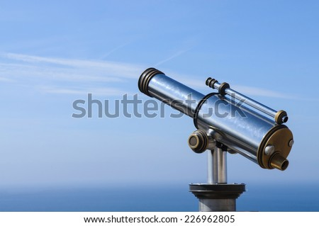 Touristic Metal Spyglass on the sky background, View on the mediterranean sea. Copy spase
