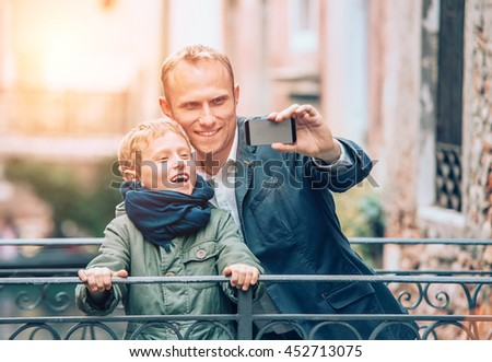 Touristic selfie - father and son take a picture with a smartphone - stock photo