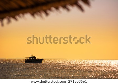 Touristic ship on the horizon at sunset and cropped part of an umbrella - stock photo