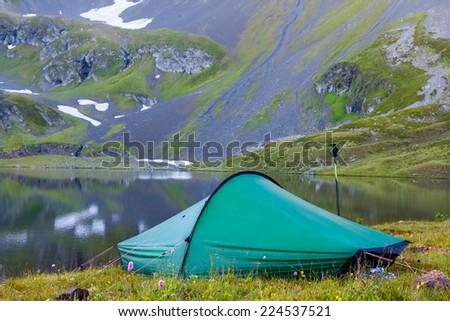 touristic tent near a mountain lake - stock photo