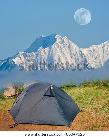 touristic tent neat a rock in a snow - stock photo
