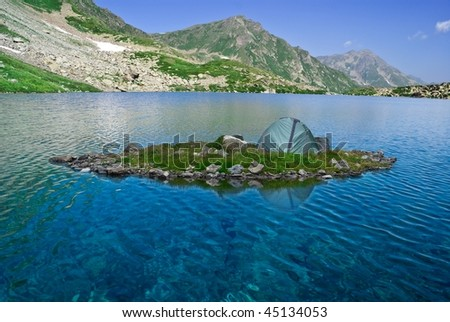 touristic tent on a island in a mountains lake - stock photo