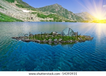 touristic tent on a island in a rays of rising sun - stock photo