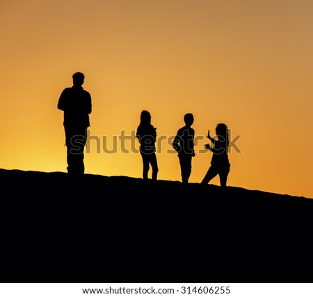 Tourists admire the setting Sun in dunes in the Atacama Desert at sunset - Oasis of Huacachina, Peru, South America - stock photo