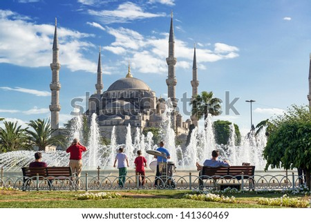 Tourists admiring the view of the fountain and Blue Mosque (Sultanahmet Camii) in Istanbul, Turkey - stock photo
