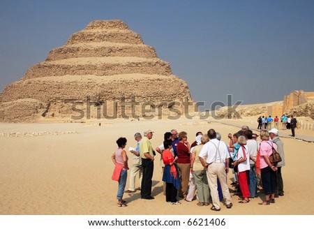 Tourists and Ancient step pyramid of Djoser (Zoser) at Saqqara, Egypt - Editorial - stock photo