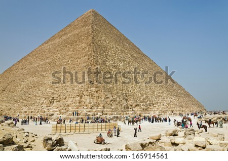 Tourists and natives are at the foot of an Egyptian pyramid. The Giza Necropolis has been a popular tourist destination since antiquity. - stock photo