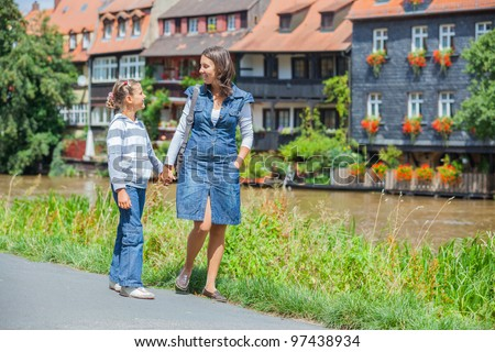 Tourists. Beautiful mother and daughter walking in europe city. - stock photo