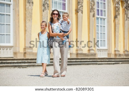 Tourists. Beautiful mother and her child walking in Sans Souci - stock photo