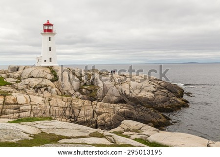 Tourists below the Lighthouse at Peggy's Cove add scale to the image.  Cloudy day with Bay of Fundy background. - stock photo