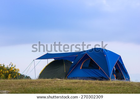Tourists blue tent on mountain and blue sky - stock photo