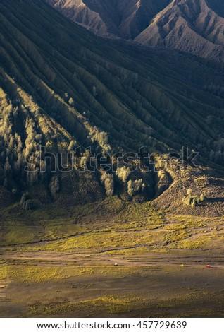 Tourists car rent pass Mount Bromo volcanoes in Bromo Tengger Semeru National Park, East Java, Indonesia. - stock photo