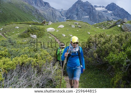 tourists coming down from the mountains in dense thickets on a summer day