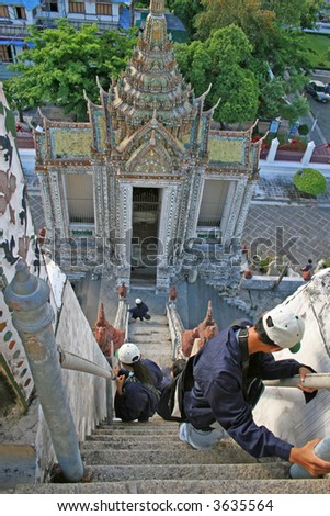 Tourists descending the steep steps of Wat Arun in Bangkok