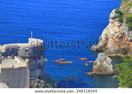 Tourists during kayak trip outside the walls of the old town of Dubrovnik, Croatia - stock photo