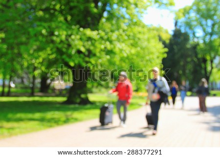 Tourists early in the morning going through empty summer park, blurred background - stock photo