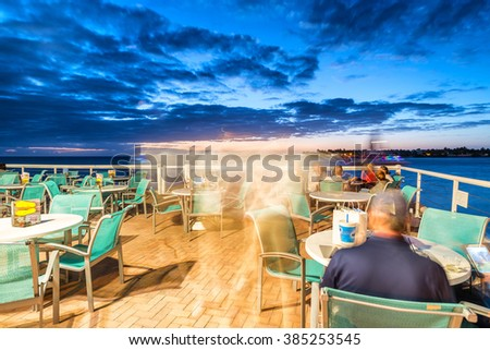 Tourists enjoying sunset in a cafe over the ocean. - stock photo