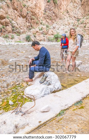 Tourists enjoying Todgha river in Todgha Gorge, Morocco - stock photo