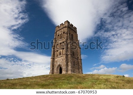 Tourists exploring the ruins of St. Michael's Tower at the top of glastonbury tor in somerest england