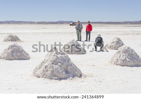 Tourists family posing among salt piles at Salar de Uyuni, Bolivia - stock photo