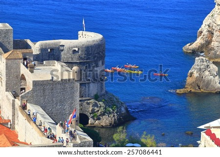 Tourists floating on kayaks around the strong walls of Dubrovnik, Croatia - stock photo