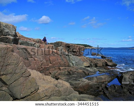 Tourists gaze in wonder at the ocean waves crashing below, in the Atlantic Ocean off Thunder Hole in Acadia National Park. - stock photo