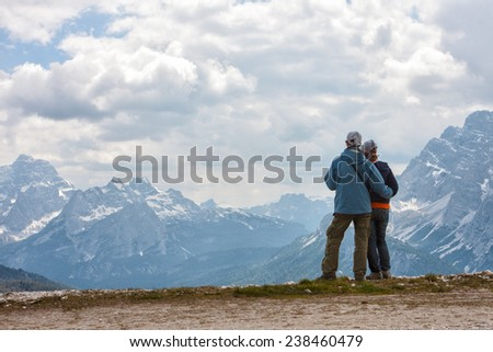 Tourists girl and man look at the mountains  - stock photo