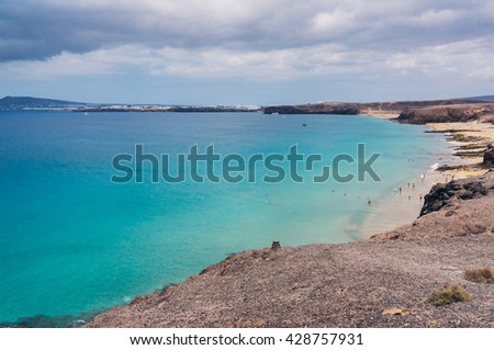 Tourists having fun in the turquoise water and on one beautiful beach in Lanzarote, Spain  - stock photo