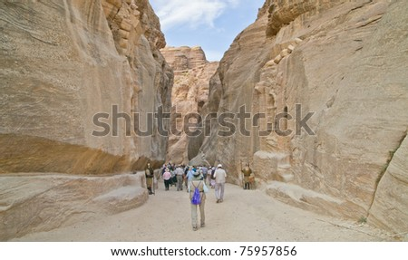 Tourists hike the ancient chasm leading to spectacular Petra,Jordan - stock photo
