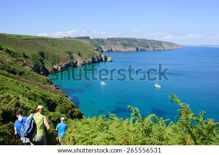 Tourists hiking  at the hills near Cap de la Chevre with a beautiful view on a bay with white sailboats. Brittany, France. Active family vacation background. - stock photo