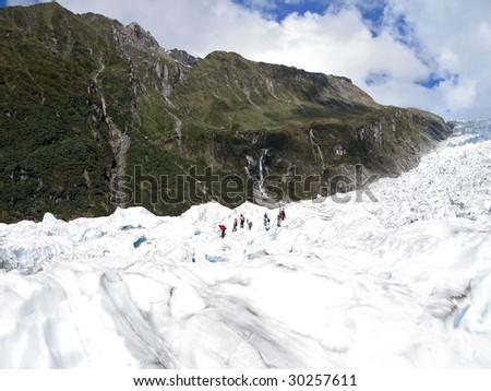 Tourists hiking on Fox Glacier, New Zealand. Te Wahipounamu World Heritage Area. - stock photo