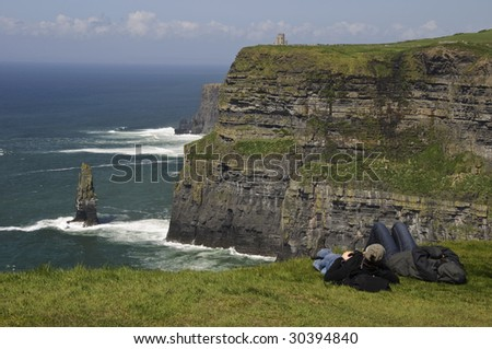 tourists holiday by seascape landscape at cliffs of moher, county clare, Ireland. wild atlantic way - stock photo