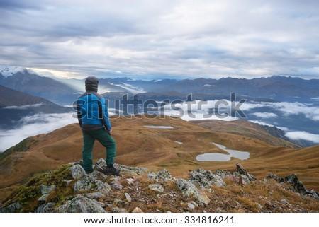 Tourists in a hike. Mountain landscape. View of the lake Koruldi. Main Caucasian ridge. Zemo Svaneti, Georgia  - stock photo