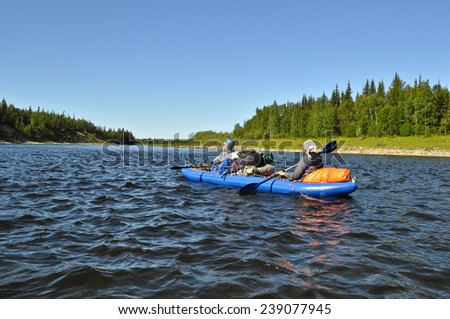 Tourists in a kayak. The boat travelers sailing on the distant Ural river.