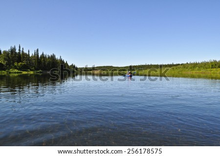 Tourists in a kayak. The boat travelers sailing on the distant Ural river. - stock photo