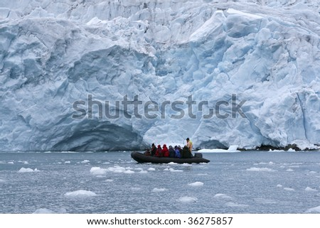 Tourists in front of a glacier in Napassorsuaq Fjord, Greenland - stock photo