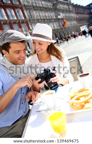 Tourists in Madrid checking on image shots - stock photo
