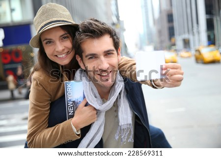Tourists in Manhattan showing New York pass - stock photo