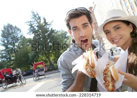 Tourists in New York city eating hot dogs - stock photo