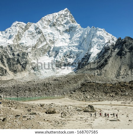 Tourists in the campaign against the backdrop of mount Everest (8848 m) and Nuptse from slope of Kala Patthar - Nepal, Himalayas - stock photo