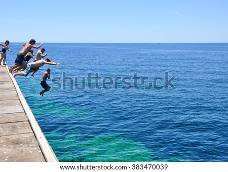 Tourists jumping off the Busselton Jetty in Western Australia/Jumping In/BUSSELTON,WA,AUSTRALIA-JANUARY 15,2016:Tourists leaping off Busselton Jetty into Indian Ocean in Busselton, Western Australia.  - stock photo