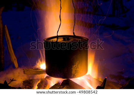 Tourists kettle on hot campfire - stock photo