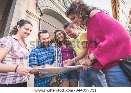 Tourists looking at city map with typical Italian street on background.
