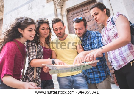 Tourists looking at city map with typical Italian street on background. - stock photo
