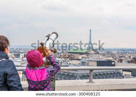 Tourists looking over Paris landscape on Lafayette Gallery terrace with telescope - stock photo
