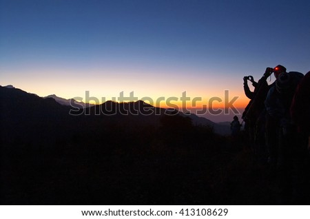 Tourists meet the sunrise at top of Poon Hill and take photos iof beautiful Himalayas, Nepal