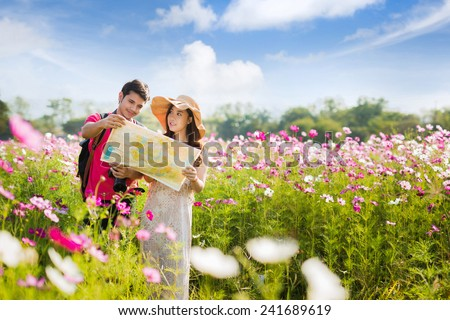 Tourists, men and women are looking at maps. In the meadow with flowers Cosmos - stock photo