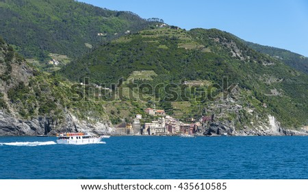 Tourists on a boat arriving to Vernazza, one of the five towns that make up the Cinque Terre region - stock photo