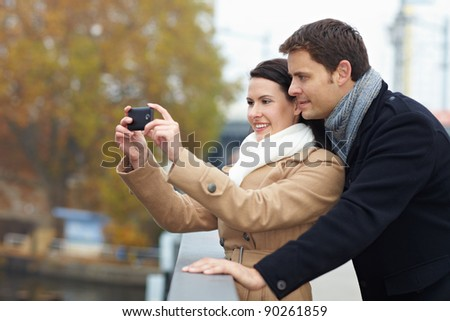 Tourists on a city trip taking photos with smartphone - stock photo