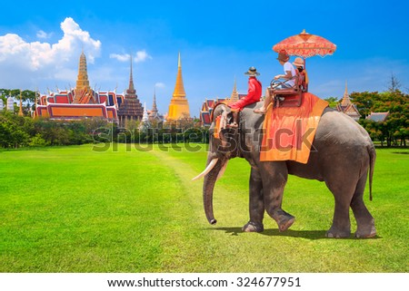 Tourists on an ride elephant dressing tradition at the Buddhist temple of Wat Phra Kaeo at the Grand Palace in Bangkok,Thailand - stock photo
